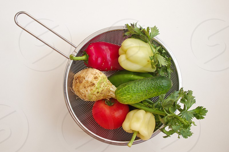 Directly above shot of the colorful vegetables in a colander against the white background photo
