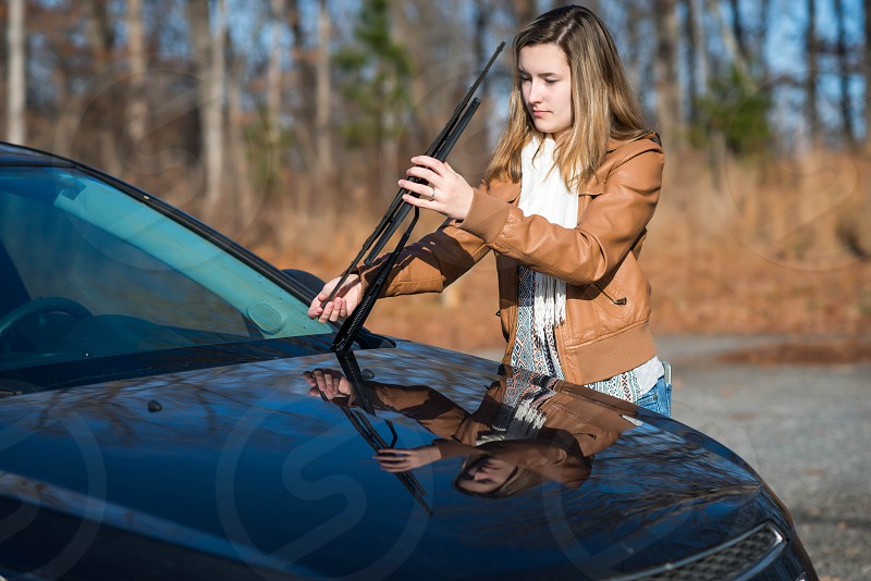 woman wearing brown leather jacket fixing car wiper photo