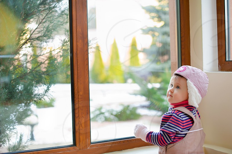 child in pink jumper wearing purple knit cap in front of brown wooden framed window during daytime photo