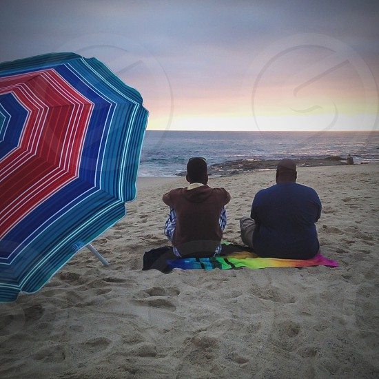 two men sitting on beach sands photo