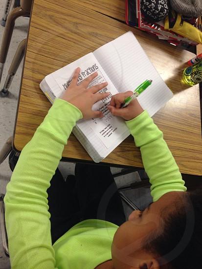 kid writing a white book photo