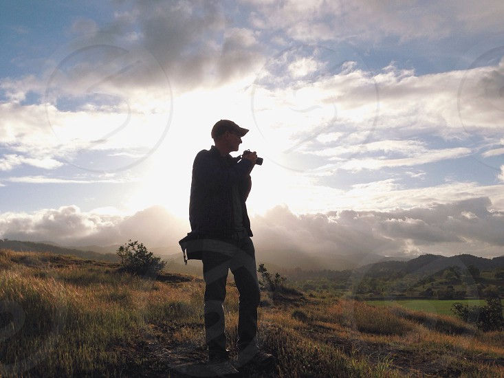 man taking a photograph in a grassy field in front of a mountain range photo