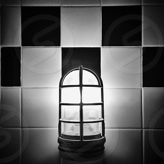 grayscale photo of turn on wall mounted lamp on black and white checked tile wall photo