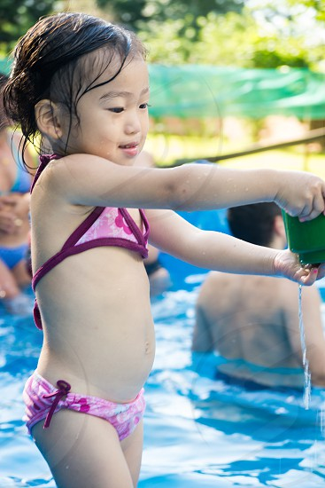 baby girl holding green container with water pouring water to the pool photo