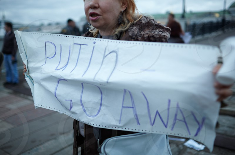 MOSCOW-MAY 6: A woman holds a placard with inscription Putin Go Away during a protest rally organized to free prisoners of conscience on May 6 2013 in Moscow Russia. photo