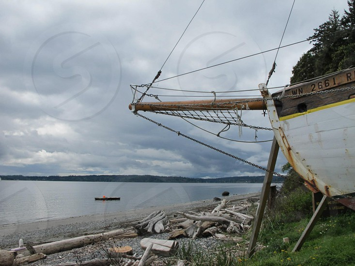 Portion of old sailboat projected onto driftwood beach dark cloudy skies and water. photo