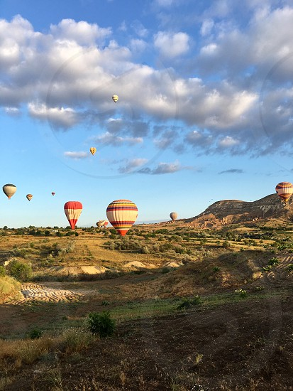 Cappadocia Goreme Turkey valley field agriculture clouds sky landscape hot air balloons flying fairy tale chimneys rock formation caves adventure crop trees arid hills photo