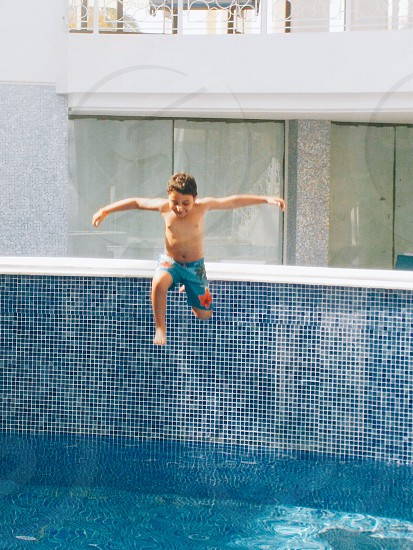 photo of boy wearing blue and orange floral shorts jump off to the pool during daytime daytime photo