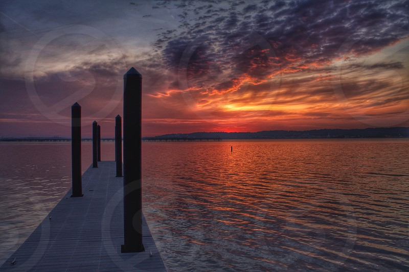 gray and black clouds over body of water across dock during orange and red sunset photo