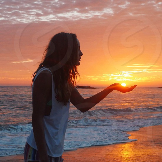 woman standing at the seashore during sunset photo