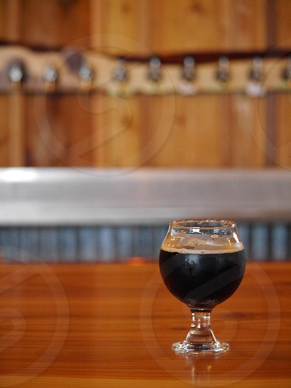 No logo up close stout beer with a wood bar in the background; craft beer; bar photo