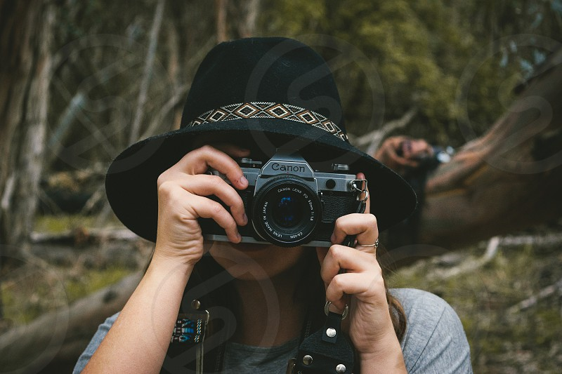 woman holding black canon dslr camera wearing black hat photo