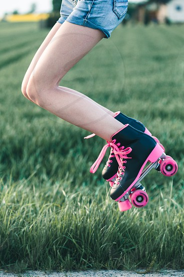 Teenage girl having fun rollerskating jumping spending time on summer day photo