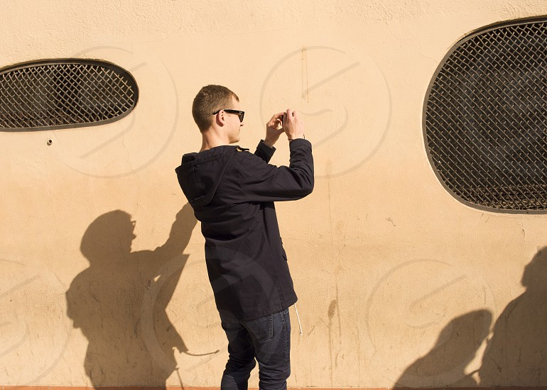 man in black jacket aiming camera by the oval window photo