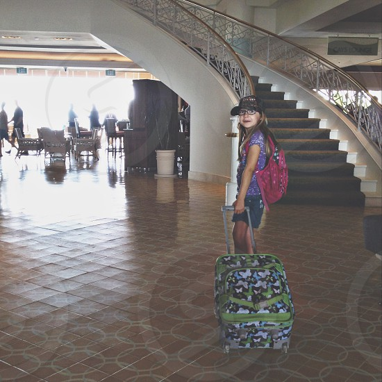 girl in red backpack holding luggage bag photo
