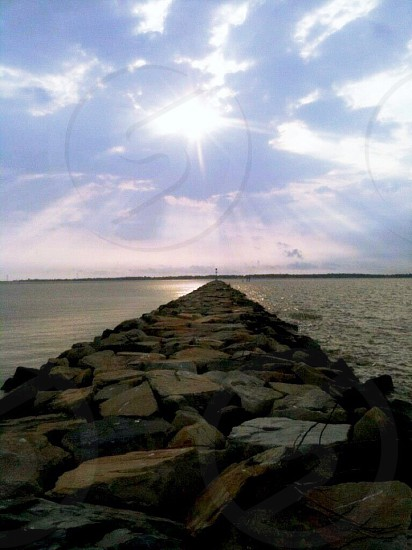 gray and brown rock boardwalk under blue sky with sun rays photo