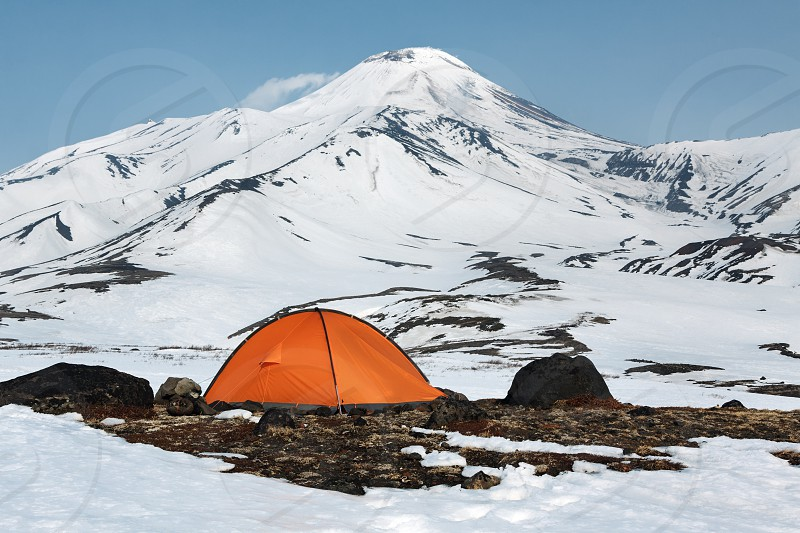 Orange camping (tourist) tent stands on meadow surrounded by snow at foot of beautiful active Avacha Volcano on Kamchatka Peninsula in Russian Far East. photo