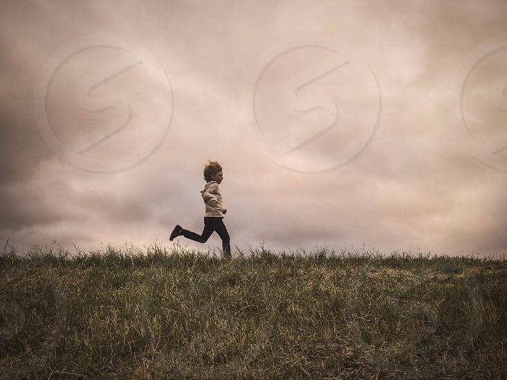 A little boy running across a grassy hill.  photo