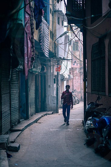 Young Indian boy walking down a narrow alley photo