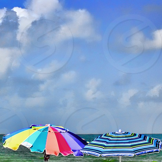 The tops of two colorful umbrellas are seen near the ocean under a blue sky with clouds. photo