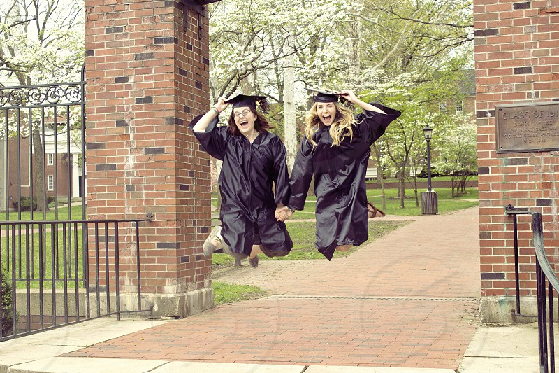 2 woman on graduation robe jumping photo