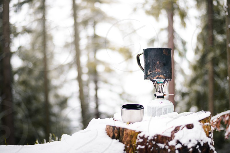 preparing food with a portable gas burner in a winter forest. hunting and hiking concept photo
