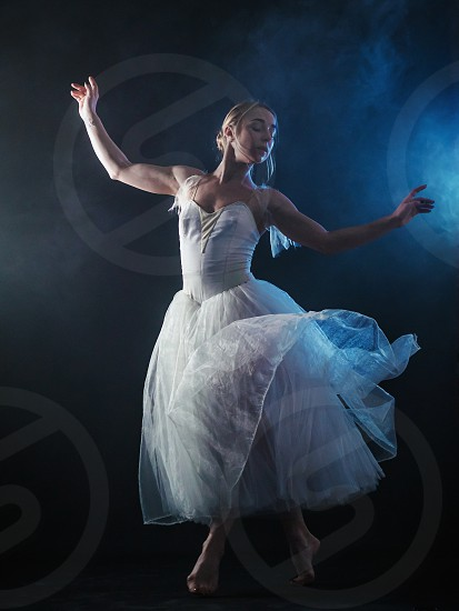 Ballerina is practicing her moves in dark studio. Young girl dancing with air white dress tutu spinning around and smiling. Gracefulness and tenderness in every movement photo