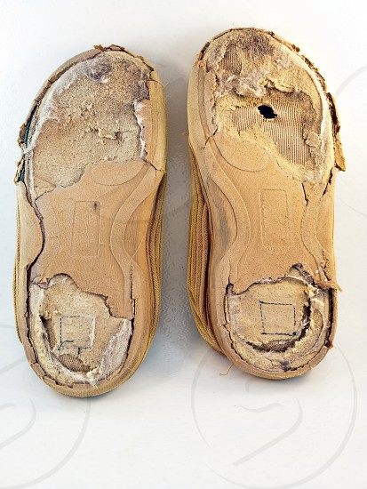 A pair of old worn out shoes isolated on a white plastic background. photo