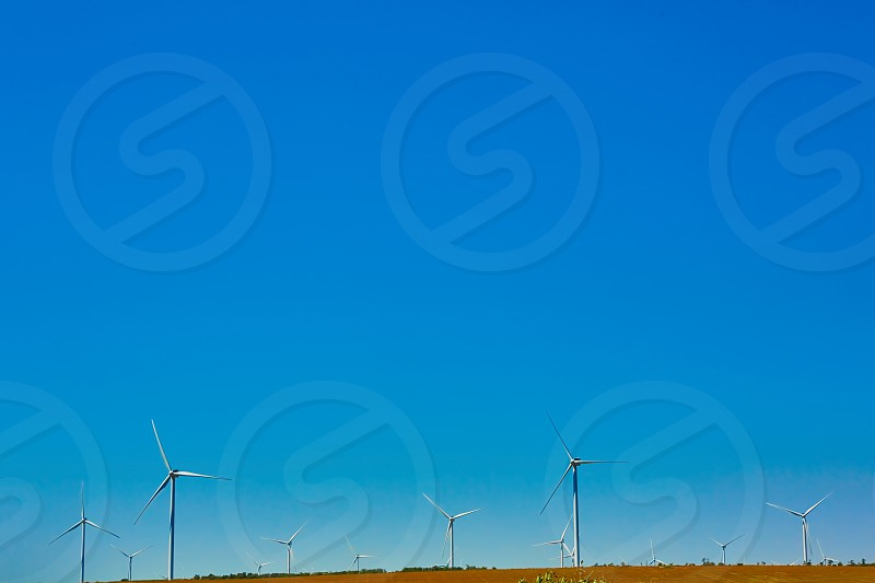 windmill in a landscape under white clouds and blue sky during daytime photo
