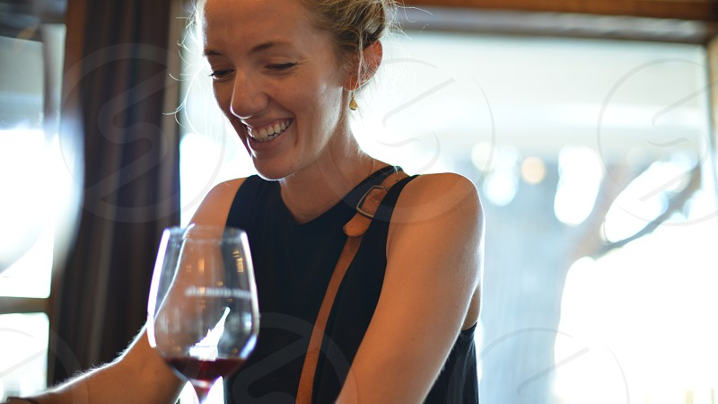 young woman holding glass of red wine • woman. happy. glass of wine. photo