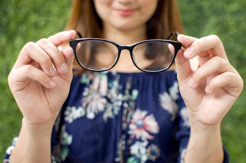 Woman holding eyeglasses photo
