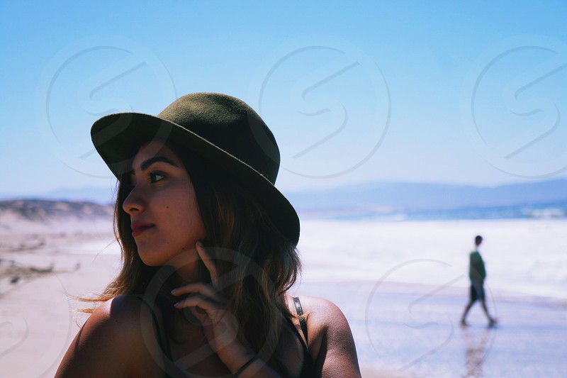 beach day sunny hat woman lady girl ocean water sand mountains looking away bay  photo
