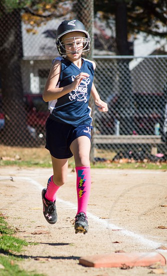 girl running in helmet and cleats photo