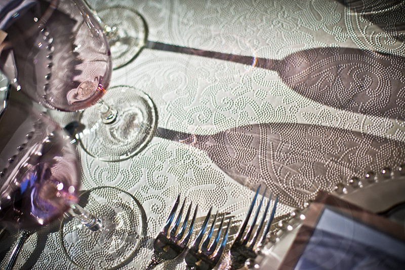 Abstract detail closeup macro table cloth fancy luxury reception party rose flutes glasses stemware silverware forks plate sun glass color texture cream feminine design dinner dining wine champagne  photo
