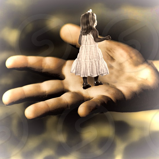 Fantasy image of a tiny girl standing in an open hand. photo
