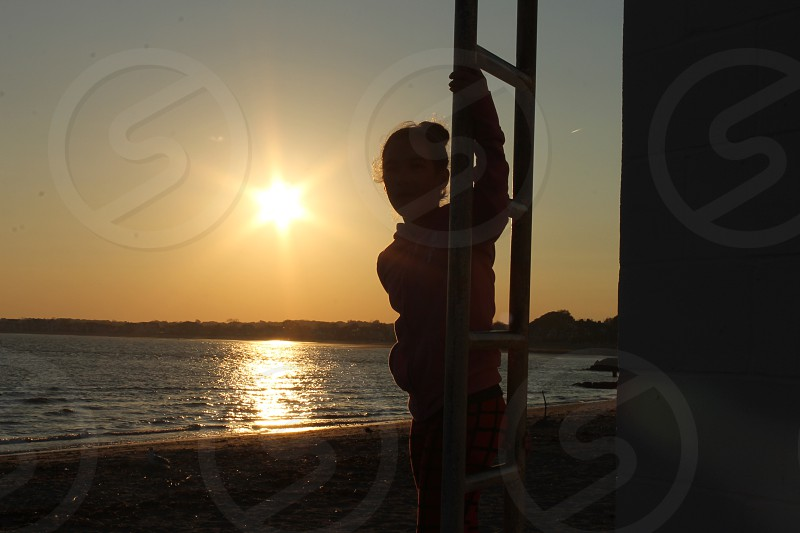 silhouette of person climbing ladder near seashore during sunset photo