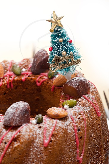 Christmas cake donut with tree as festive decoration on top over white background photo