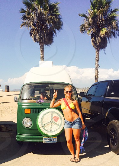 female in yellow bikini blue denim shorts giving denim shorts by green volkswagen van photo
