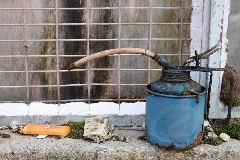 blue gas tank beside grey steel fence photo