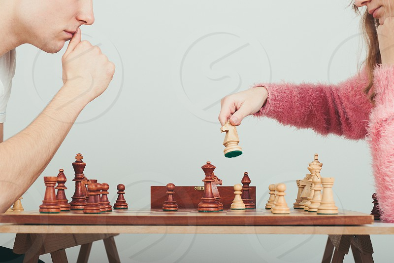 Girl and boy playing chess at home. Girl moving her piece. Teenagers sitting by a table. Profile view. Copy space for text at the top and bottom of image photo