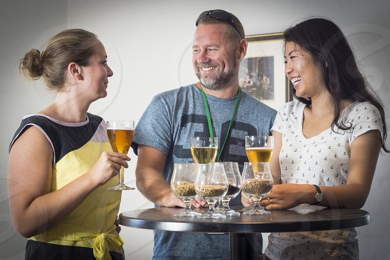 three friends happily taste beer after an historical brewery tour next to glasses with various beer ingredients photo