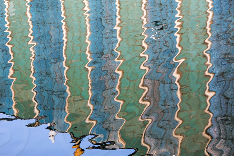 A striped blue and turquoise green facade and sky reflecting in water photo