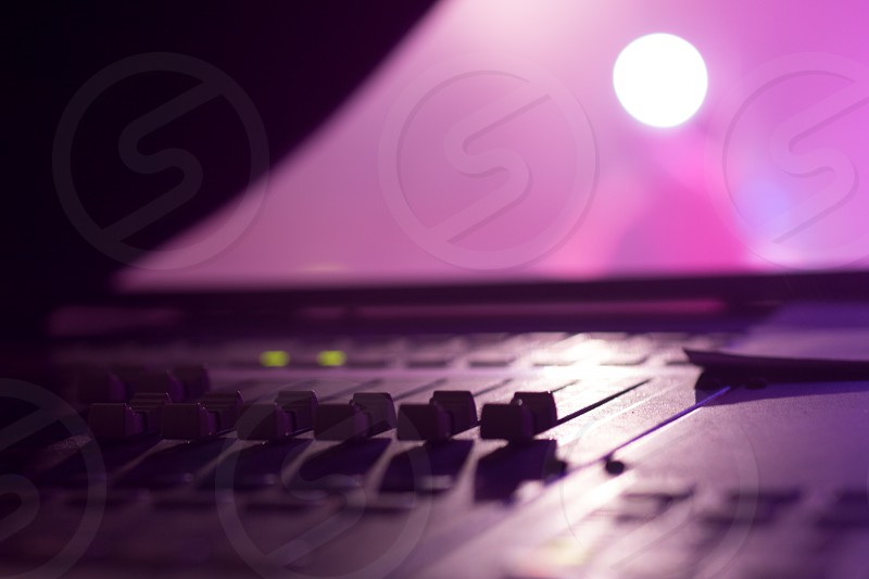 Stage side Low level view of Faders on a Professional Audio Sound Mixing Console at music festival black Faders and pink purple background photo