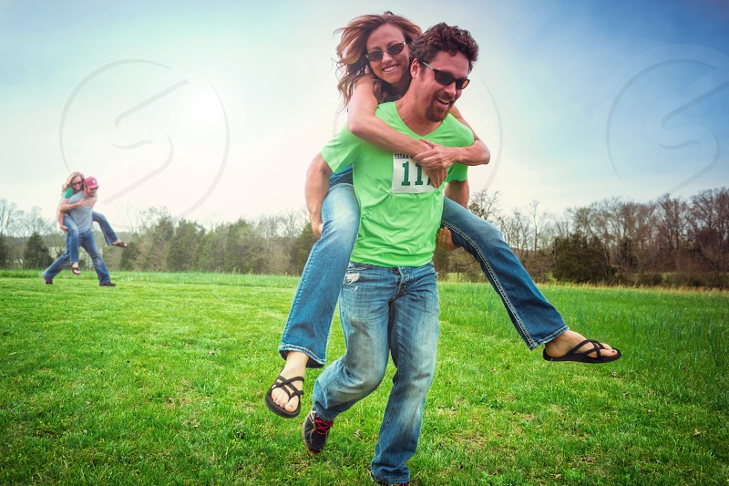man in green v neck t-shirt carrying woman at his back while running on green field photo