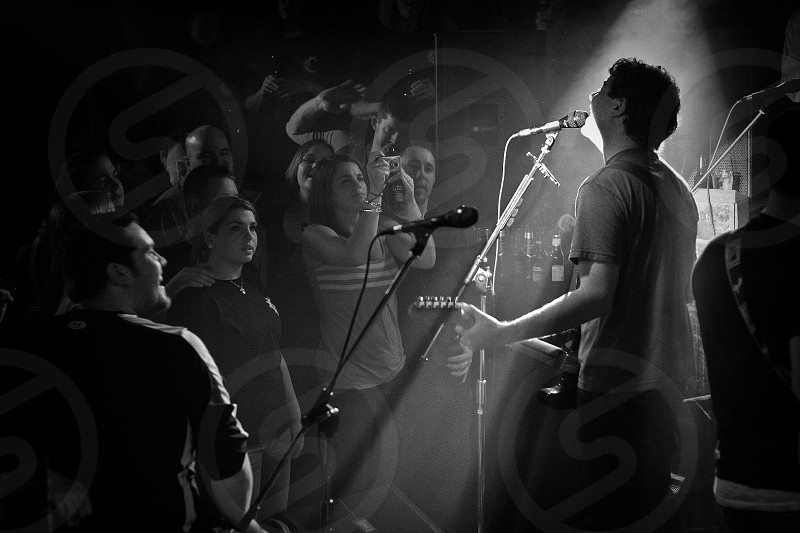 grayscale photography of man performing on stage and people cheering for him photo