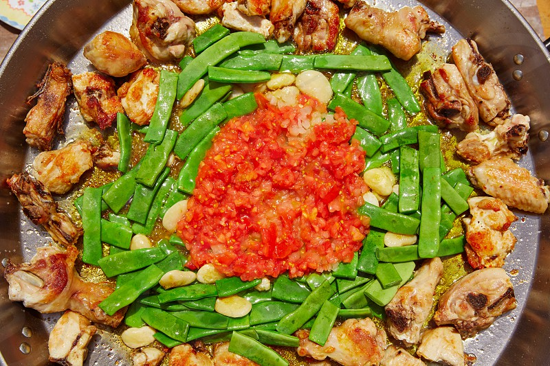 Paella from Spain recipe process ad vegetables green beans and tomato photo