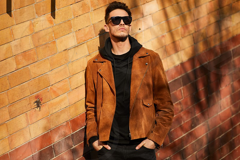 Model looking man stand near the wall and hold his glasses towards the sun shine photo