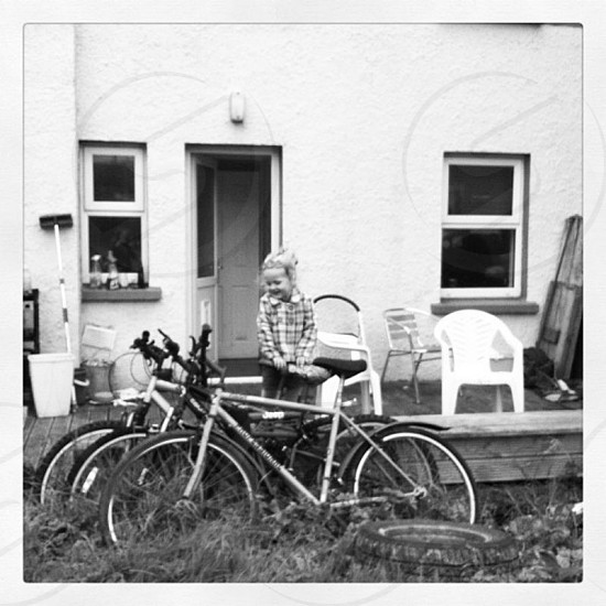 my daughter in back yard near bicycles black and white photo photo