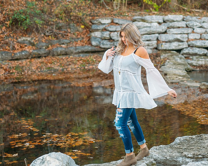 Teen girl happily walking and balancing on rocks by a creek. photo