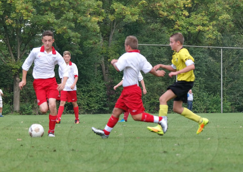 boy's playing football with red and white uniforms against yellow and black uniform photo
